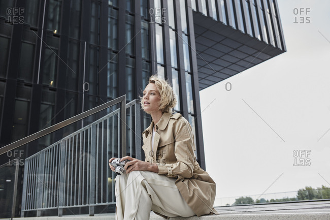 Portrait of young blond woman with digital camera sitting on stairs