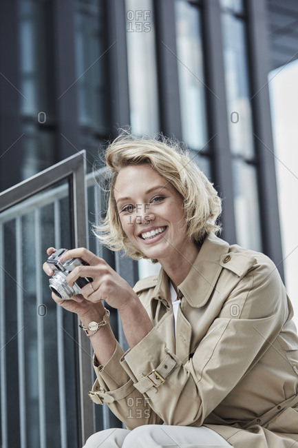 Portrait of smiling young blond woman with digital camera sitting on stairs