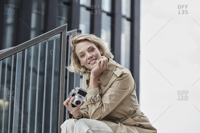 Portrait of smiling blond woman with digital camera sitting on stairs