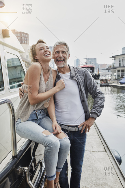 Laughing older man and young woman standing on jetty next to yacht