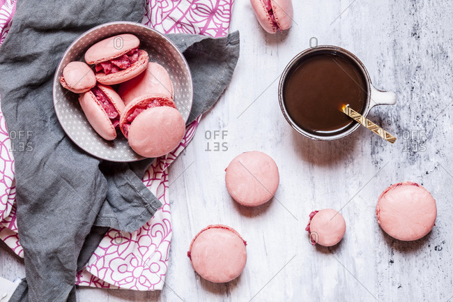 Pink macarons filled with raspberry buttercream and a cup of coffee