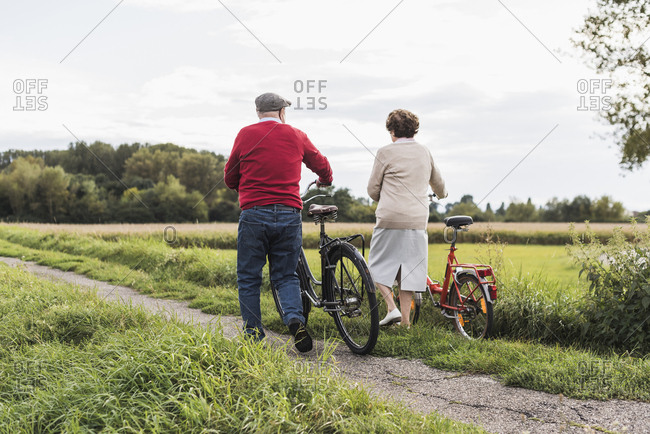 Senior couple pushing bicycles in rural landscape