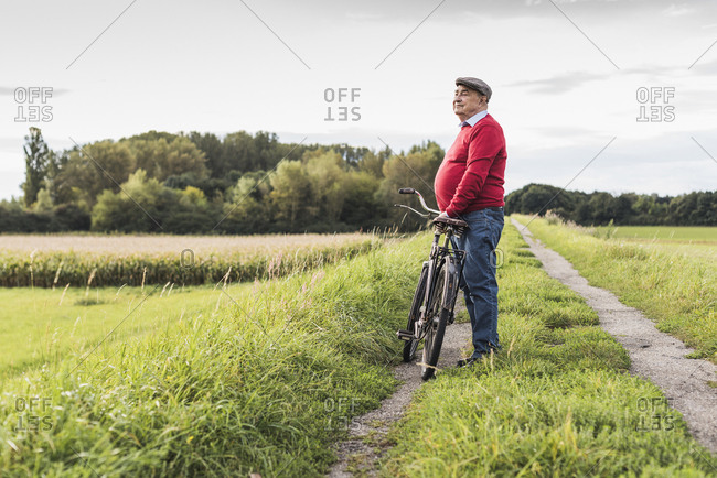 Senior man with bicycle in rural landscape