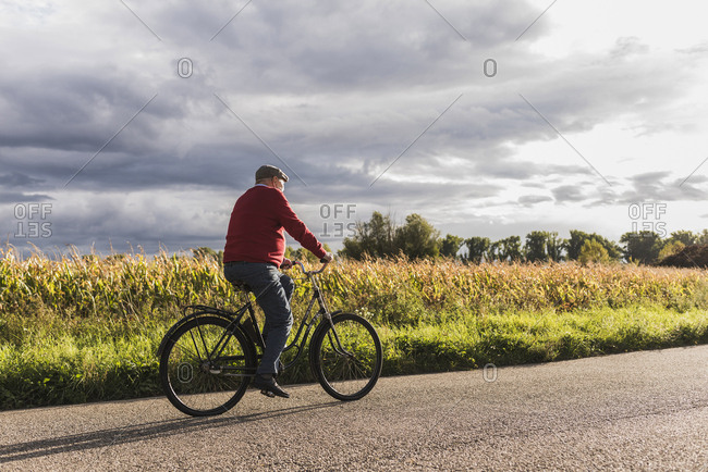Senior man riding bicycle on country lane