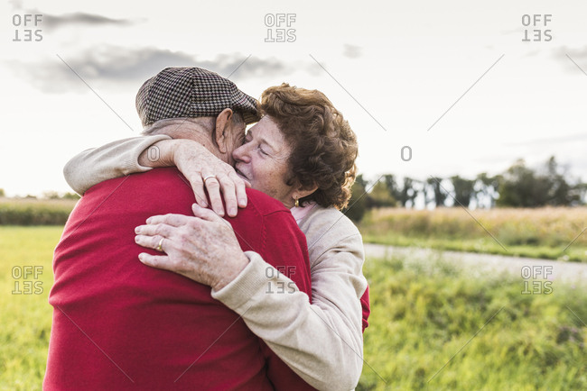 Senior couple hugging in rural landscape
