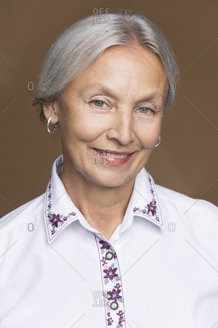 Portrait of smiling senior woman with grey hair wearing embroidered blouse