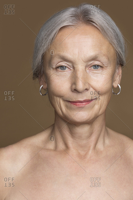 Portrait of naked senior woman with grey hair in front of brown background