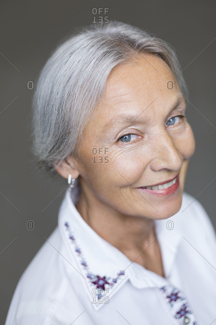 Portrait of smiling senior woman with grey hair and blue eyes