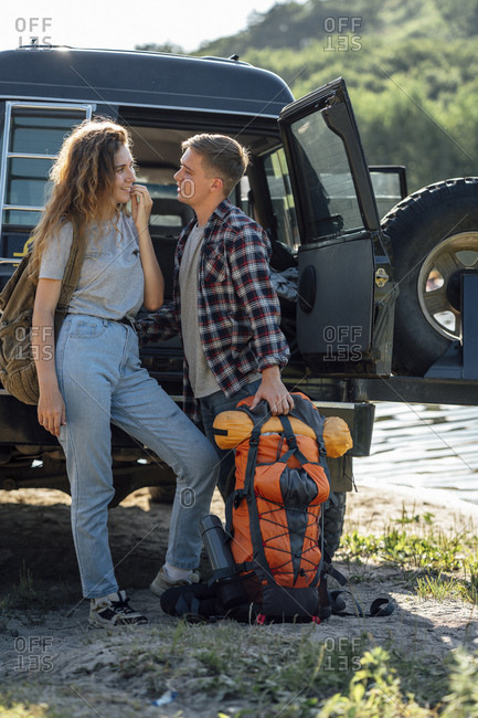 Young couple doing an outdoor trip- hiking with backpacks
