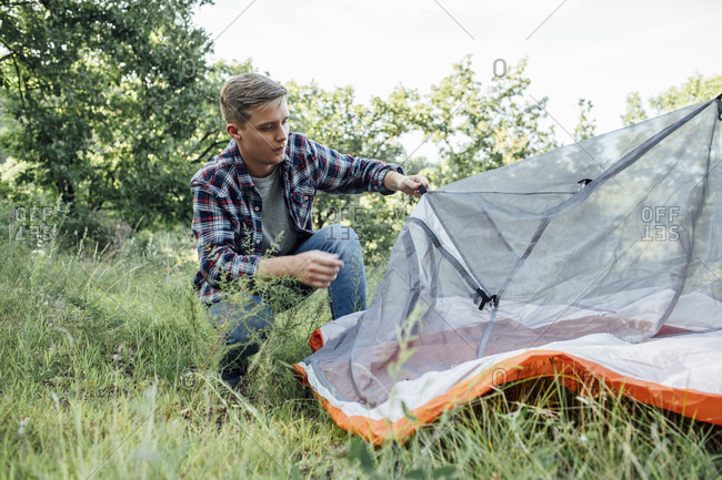 Young man camping in nature- setting up tent