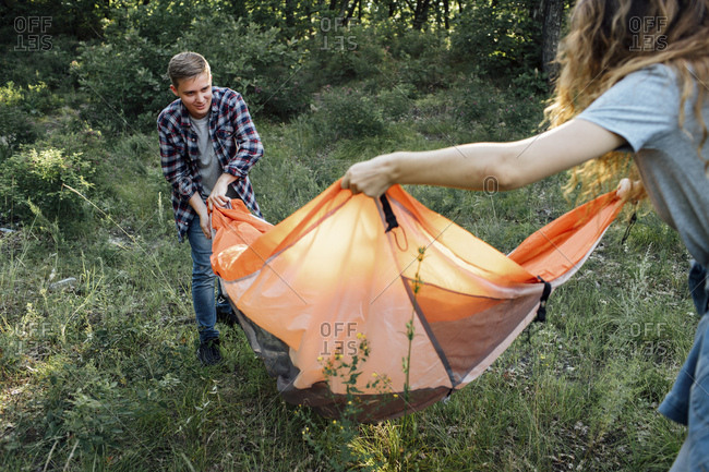 Young couple camping in nature- setting up tent