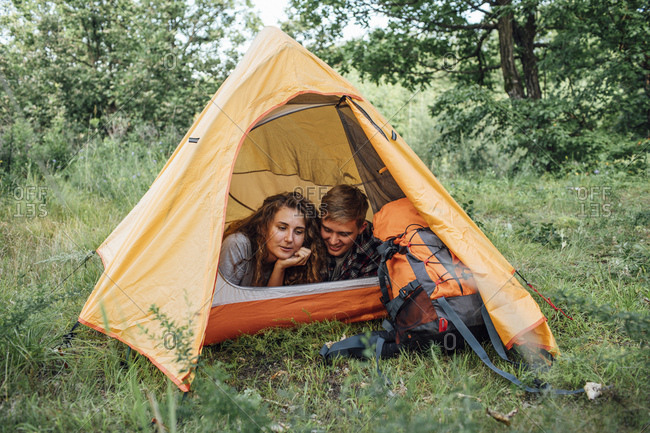Young couple camping in nature- lying in tent- taking a break
