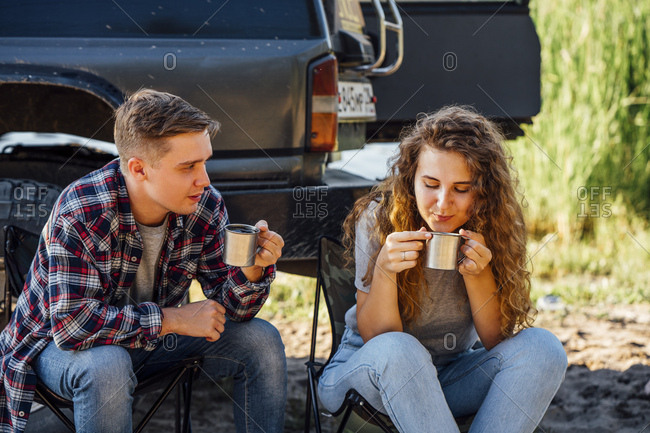 Young couple sitting by car- taking a break- drinking tea