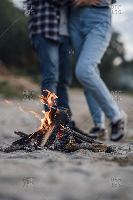Burning campfire at the riverside- couple in background