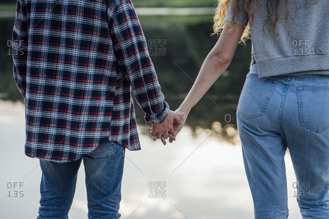 Romantic couple standing at the riverside- holding hands