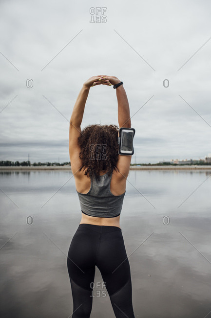 Rear view of young athletic woman stretching at the riverside
