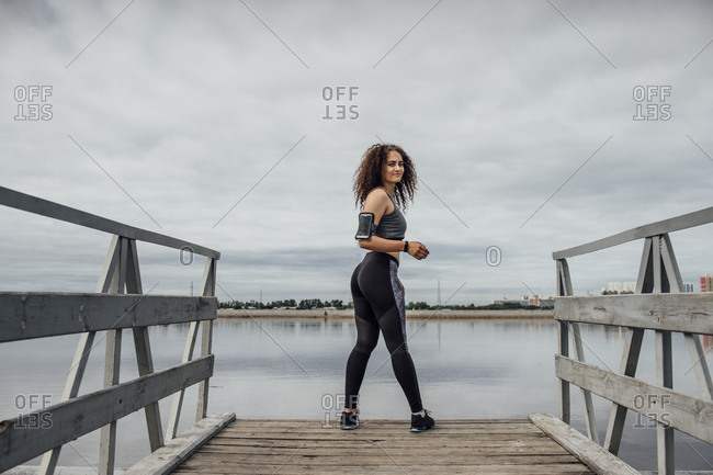 Young athletic woman standing on jetty at the riverside