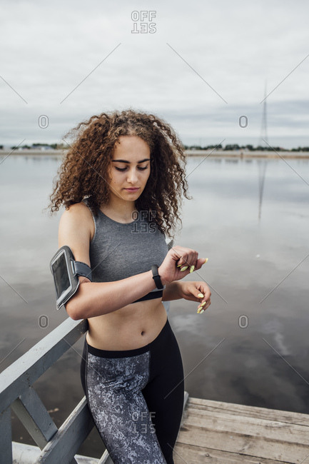 Young athletic woman at the riverside looking at wristwatch