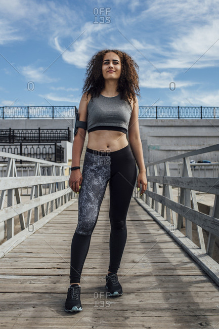 Young athletic woman standing on a pier