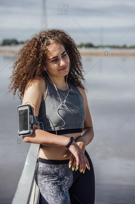 Smiling young athletic woman wearing earbuds at the riverside