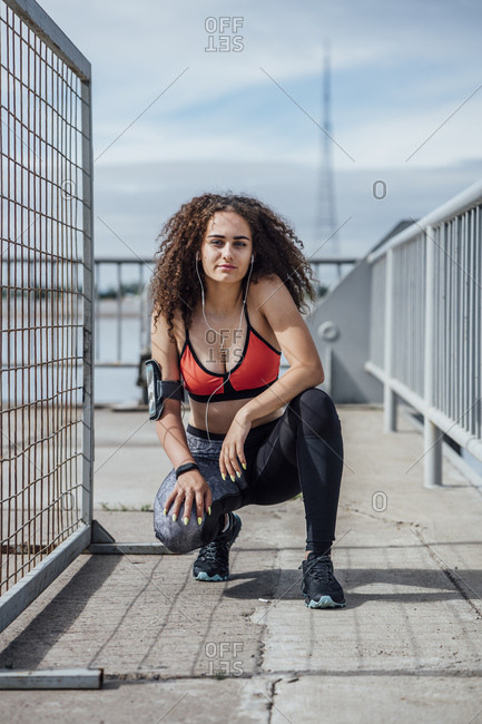 Portrait of young athletic woman with earbuds crouching outdoors