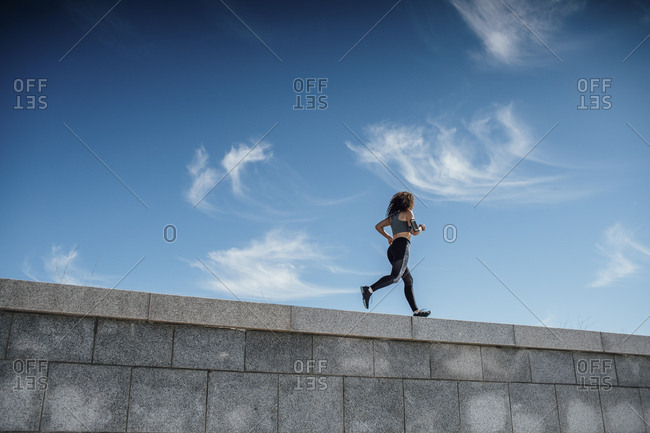 Young athletic woman running on a wall