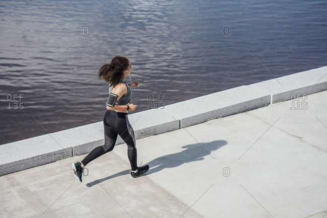 Young athletic woman running at the riverside