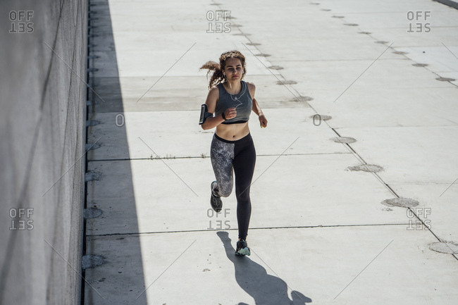 Young athletic woman running on a promenade