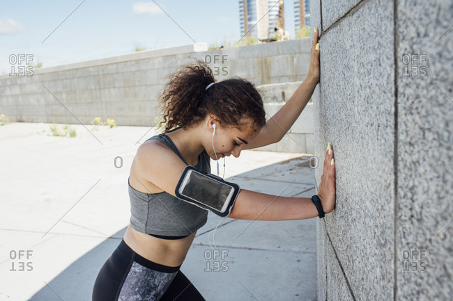 Young athletic woman listening to music leaning against a wall