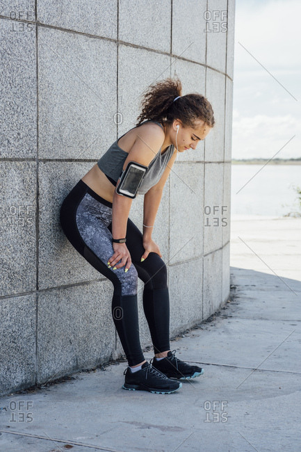 Exhausted young athletic woman wearing earbuds leaning against a wall