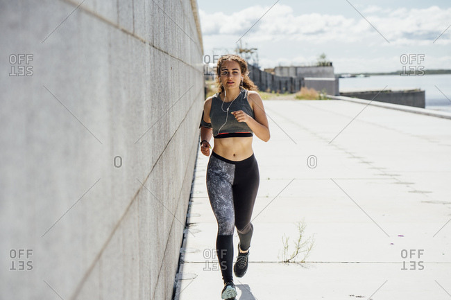 Young athletic woman running along a wall