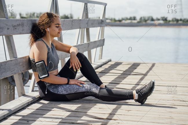 Young athletic woman wearing earbuds resting at the riverside