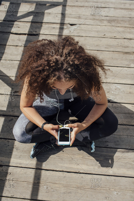 Young athletic woman sitting on boardwalk using smartphone