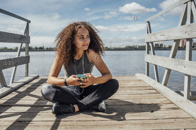 Young athletic woman sitting at the riverside using smartphone