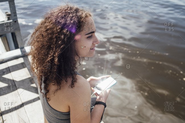 Smiling young athletic woman with smartphone at the riverside
