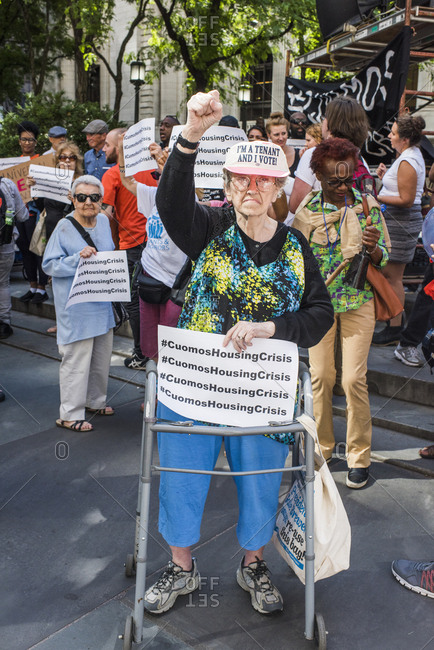 New York City, New York, USA - June 14, 2018: Senior woman with arm raised and clenched fist protesting at march to end homelessness