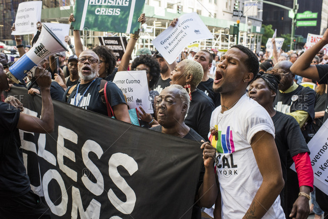New York City, New York, USA - June 14, 2018: Group of people shouting and holding signs at march to end homelessness