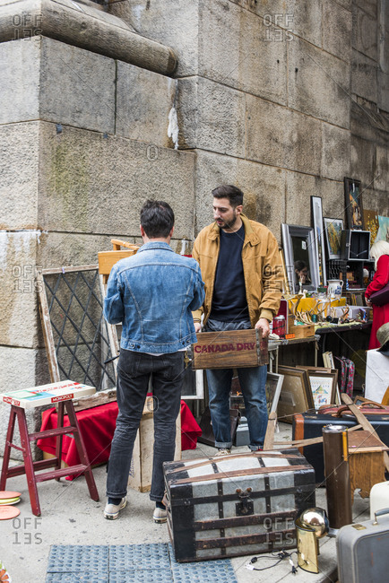 Brooklyn, New York, USA - January 20, 2018: Young men browsing antiques and collectibles for sale at the Brooklyn Flea market