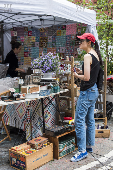 Brooklyn, New York, USA - January 20, 2018: Young woman browsing antiques and collectibles for sale at the Brooklyn Flea market
