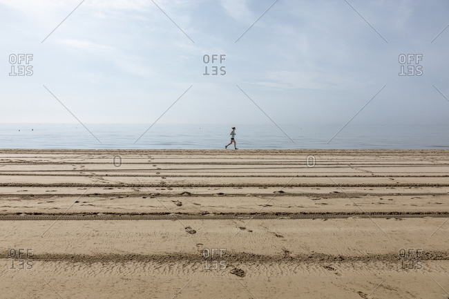 Venice, Italy - May 31, 2018: Young woman running alone on the beach at Punta Sabbioni