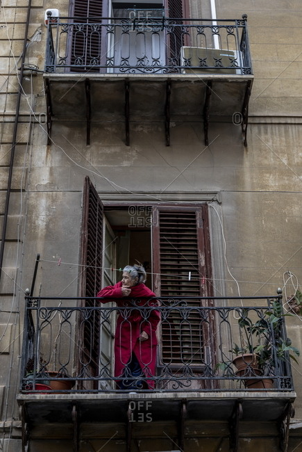 Palermo, Italy - March 7, 2018: Woman standing on balcony of historic building in the Kalsa neighborhood