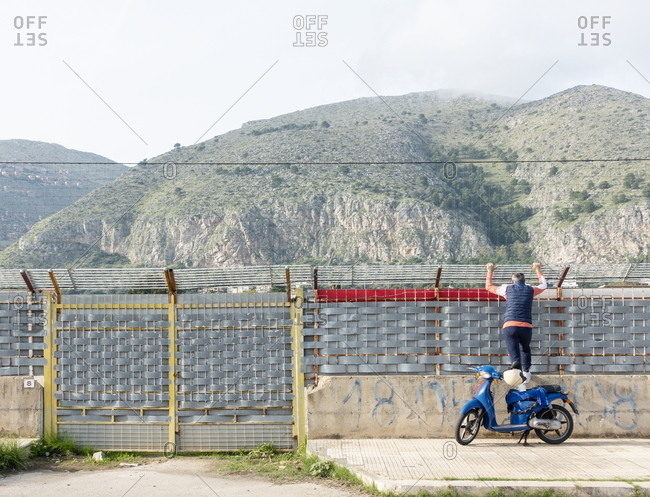 Palermo, Italy - October 20, 2018: Person looking over fence to watch football match in the Mondello neighborhood