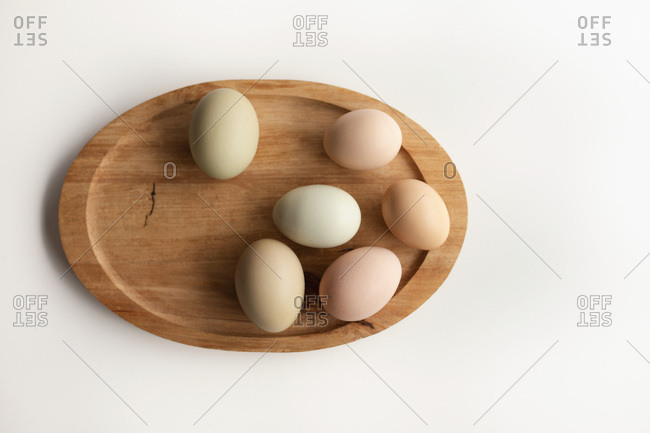 A collection of eggs in a variety of pastel colours sit on a natural wood platter.