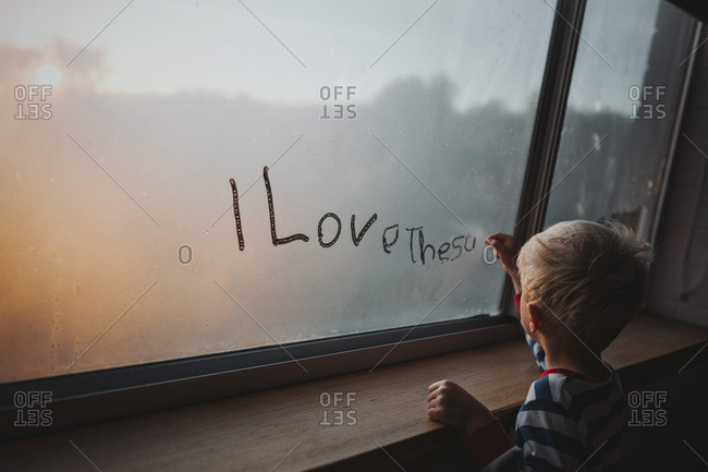 A young blonde boy writes I Love The Sun on a foggy window on a cool winter morning.