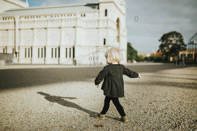 Girl walks enthusiastically in a deserted square in the city of Melbourne Australia.