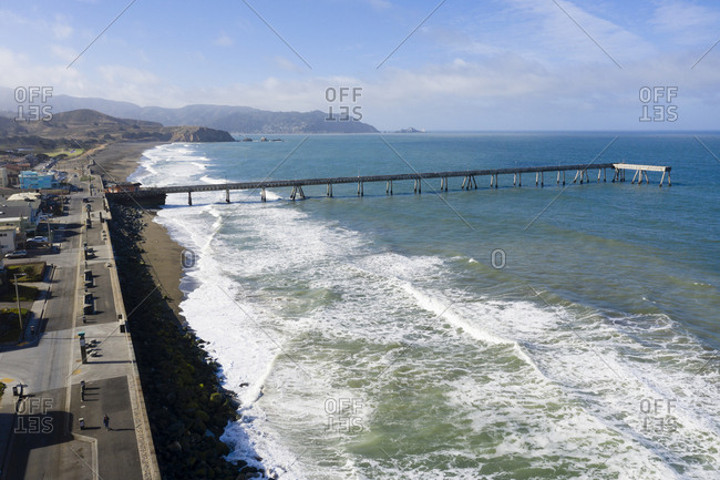 Aerial view of shoreline and distant mountains in Pacifica California