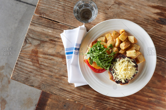 Cheddar cheese burger presented in a modern style with grated cheddar cheese that hasn't been melted, a bun with heirloom tomato and arugula sits nearby, served with chunky home fries in an upscale bistro restaurant on a rustic wooden table.