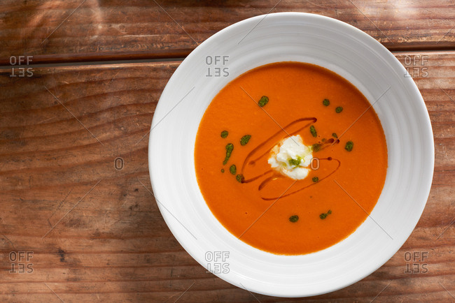 Hearty bowl of cream of tomato soup photographed from above on a wooden table.