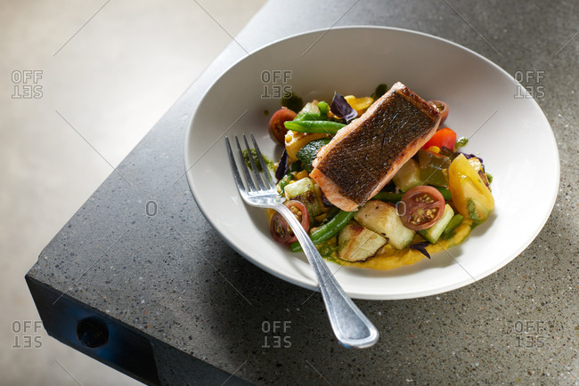 Pan Fried King Salmon served skin side up on a bed of summer vegetables including heirloom cherry tomatoes, green beans, and eggplant served on creamy polenta in a white bowl on a modern concrete surface.