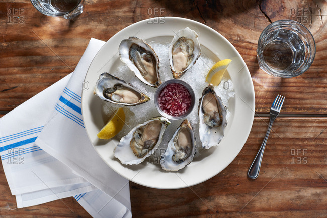 Raw oysters with a mignonette sauce on ice with a few slices of lemon on a wooden background.